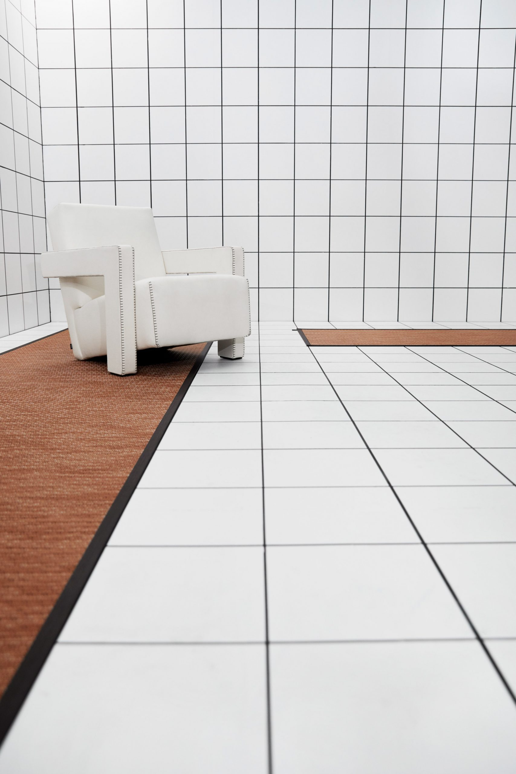 A white room with long terracotta-coloured rugs