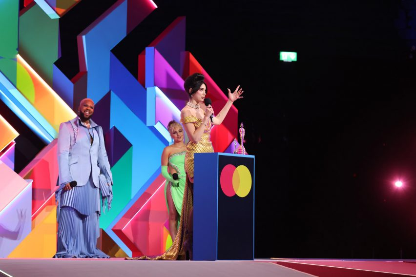 Dua Lip accepting an award in front of a multi-coloured maze-like set