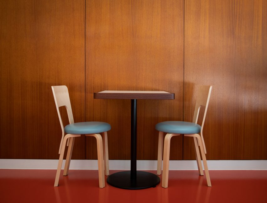 Dining chairs against wood-panelled walls in Cafe Bao