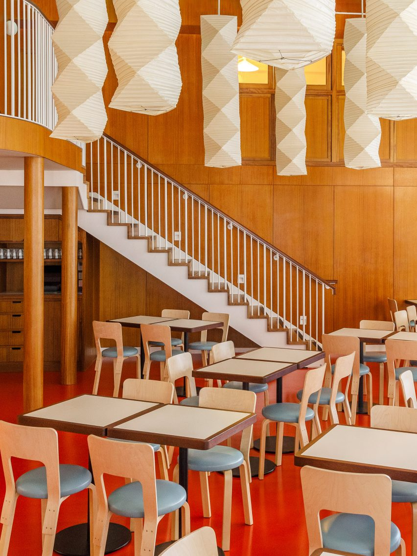 Dining area with white staircase and paper lanterns at London restaurant by Macaulay Sinclair