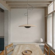 A pendant light is suspended over a dining table