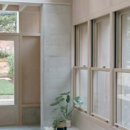 A concrete bench is located beneath the windows
