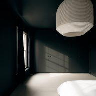 A large pendant light hangs in the bedroom