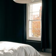 A bedroom was finished with dark walls and light carpet floors