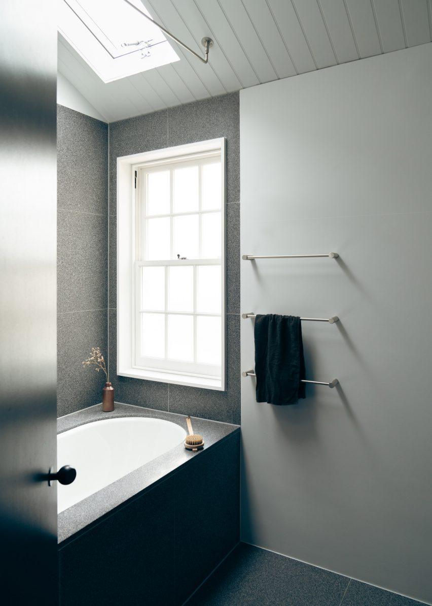 The bathroom in Concrete Plinth House employs a dark grey palette