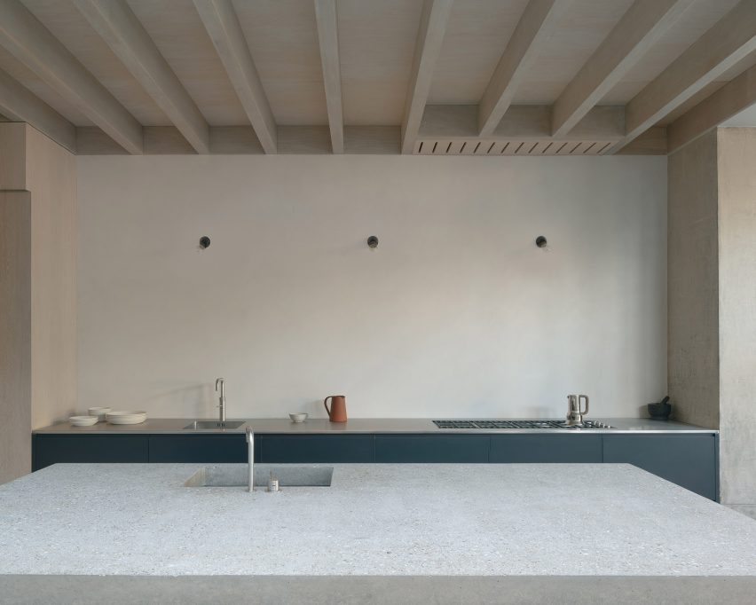 The kitchen island in Concrete Plinth House has a stone counter top