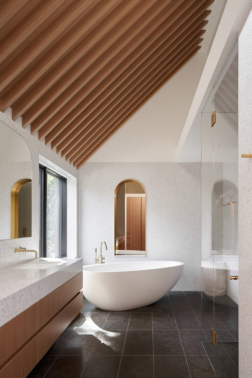 The bathroom has pink-hued marble and a curved bathtub