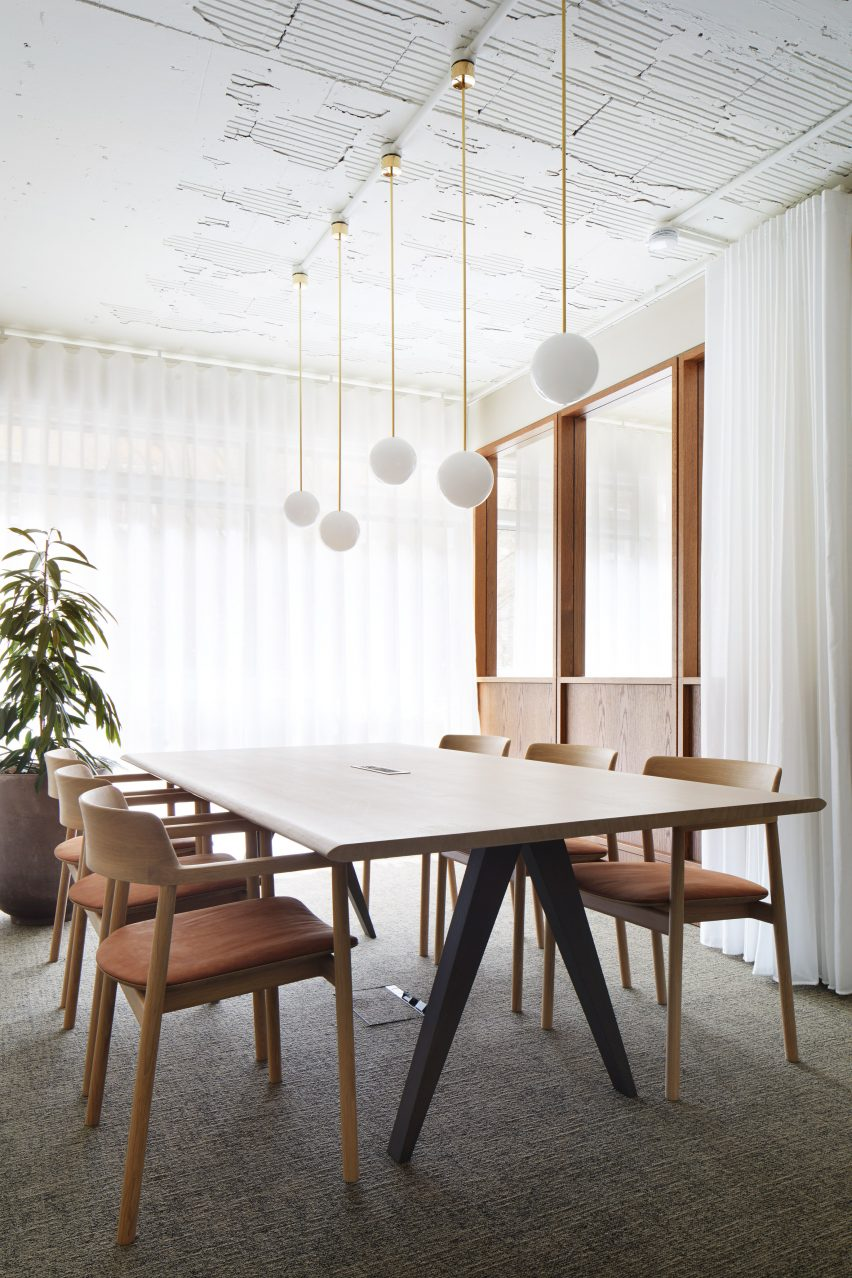 Wood-panelled meeting room with spherical pendant lights and wooden furniture in Fitzroy Street office interior