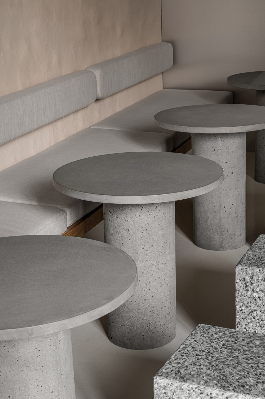 Round concrete tables and bench seating in IteIstetyka restaurant