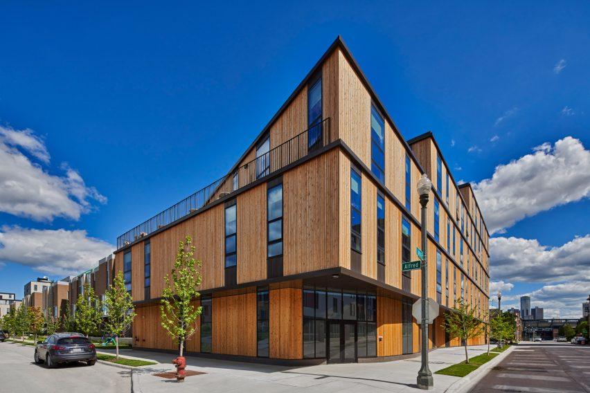 The apartment building is clad in reddish cedar