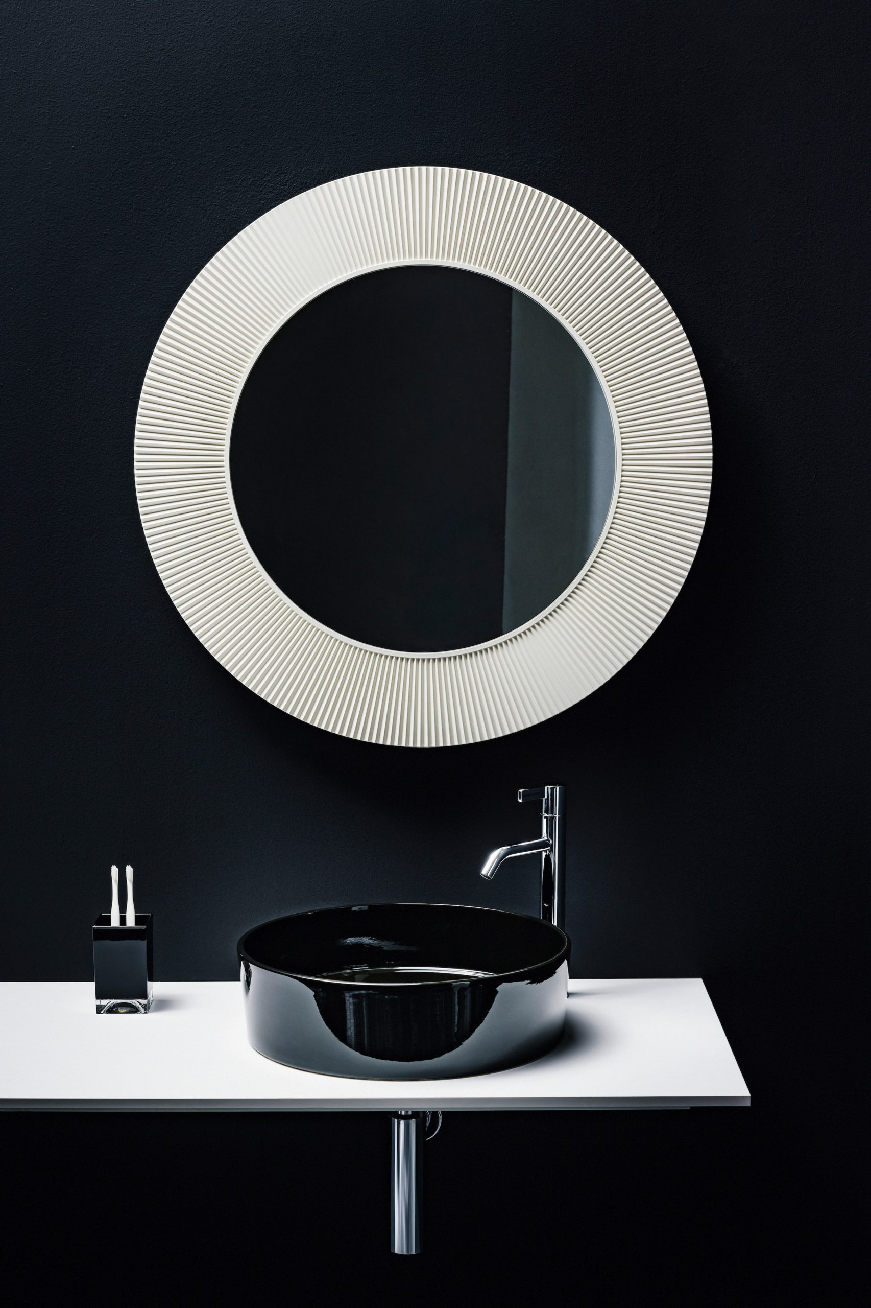 A circular bathroom mirror and sink