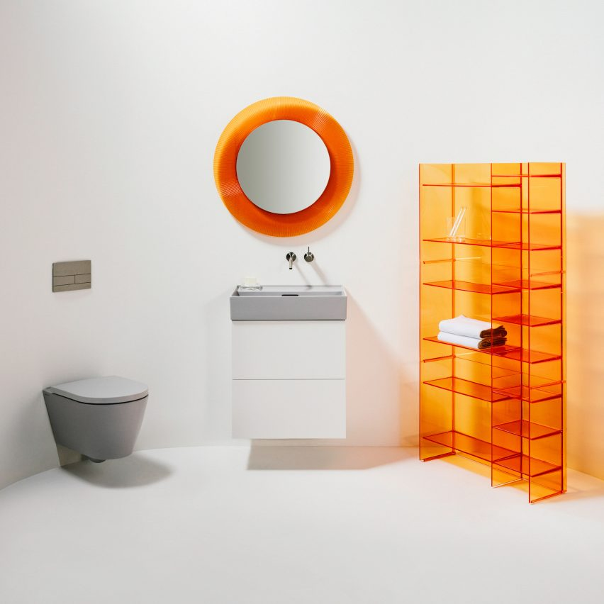 A white bathroom with orange accessories