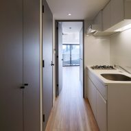 A galley kitchen is located between living spaces