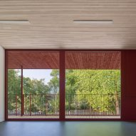 Large windows are framed by red walls