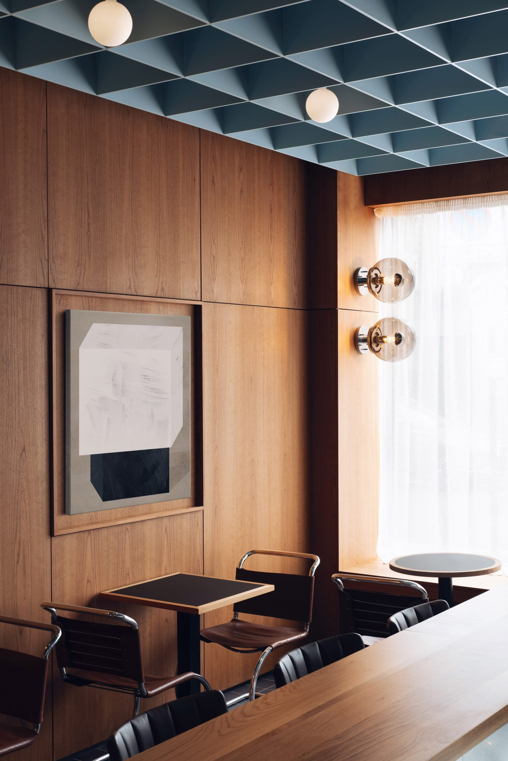 Wood-panelled walls with art in Maido restaurant
