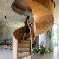 The staircase has a warm wood finish