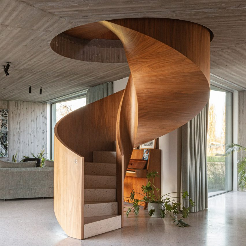A wooden spiral staircase winds through the home