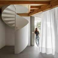 A white spiral staircase is tucked behind a curtain