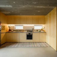 The kitchen has a light wood finish