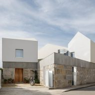 Paulo Merlini Architects perches gabled volumes on top of stone plinth at Casa Rio