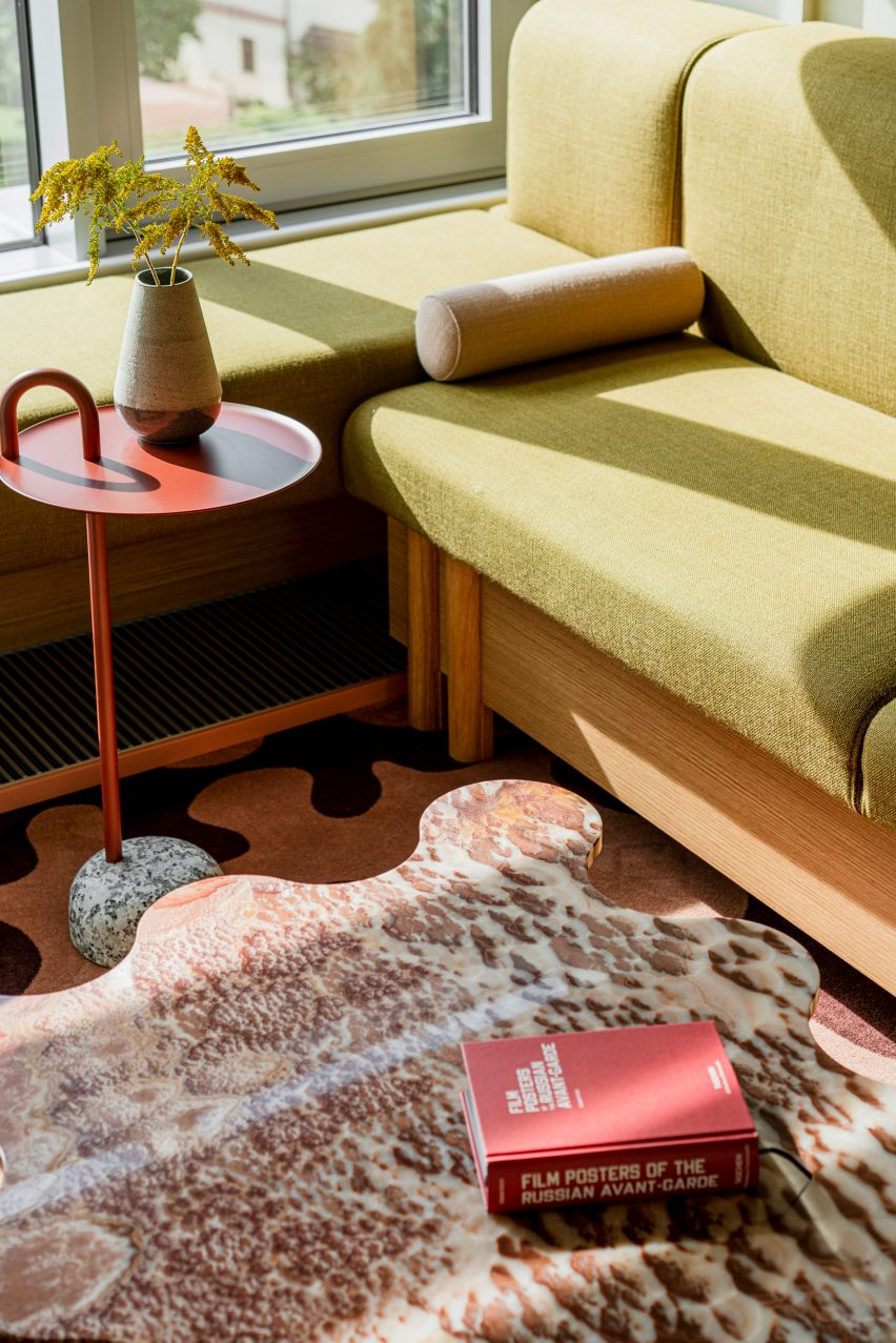Lobby with red marble table and green couch in hotel interior by Studio Paradowski