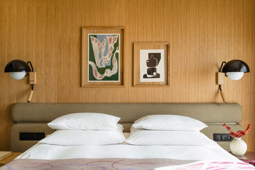 Bedroom with wooden wall panelling in hotel interior by Studio Paradowski