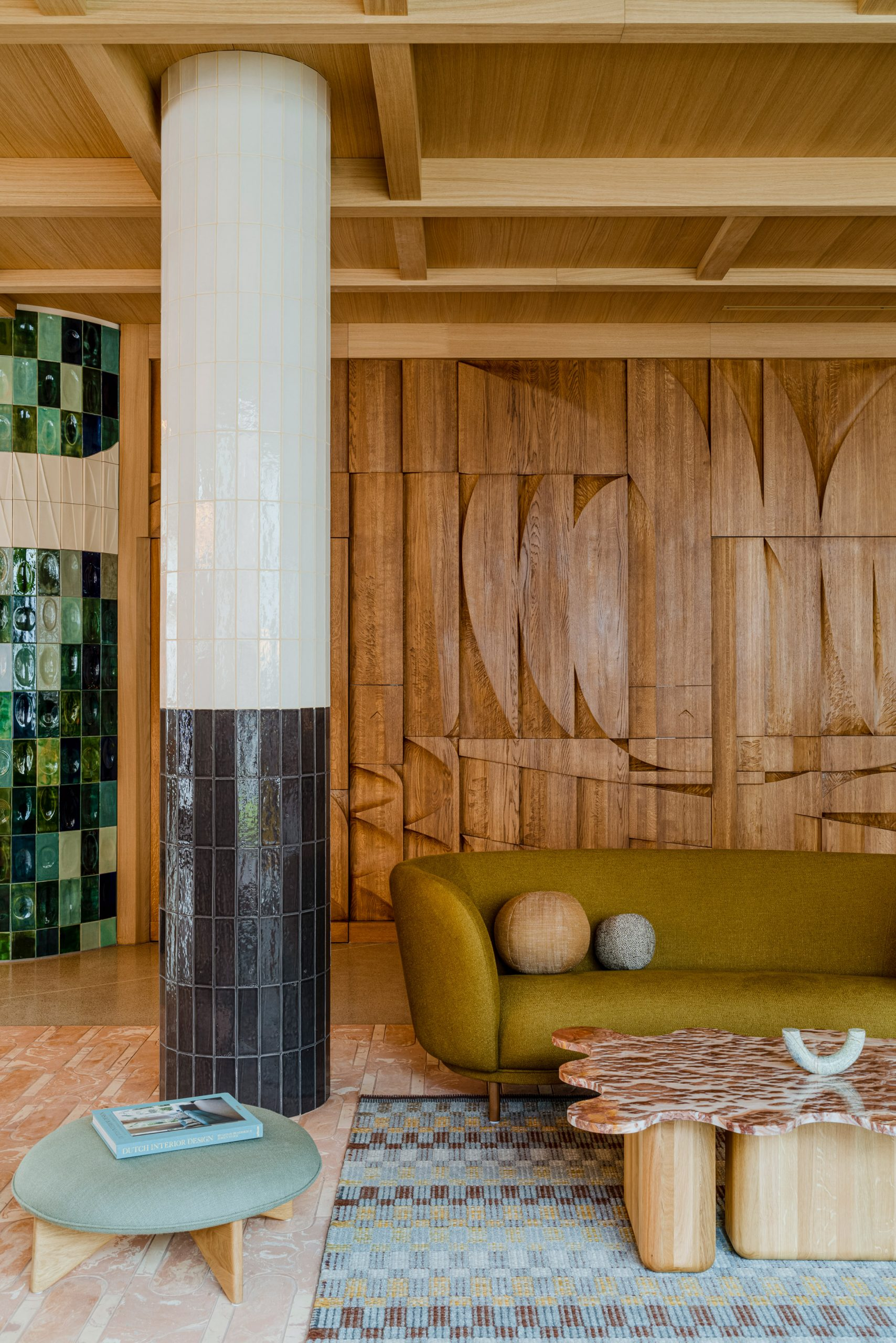 Tiled pillar and bar-relief wall in hotel interior by Studio Paradowski