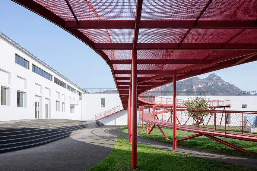 A red steel walkway in a courtyard