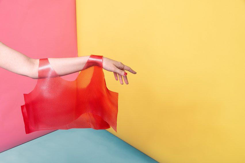 Arm holding transclucent red vest top by Valdís Steinarsdóttir
