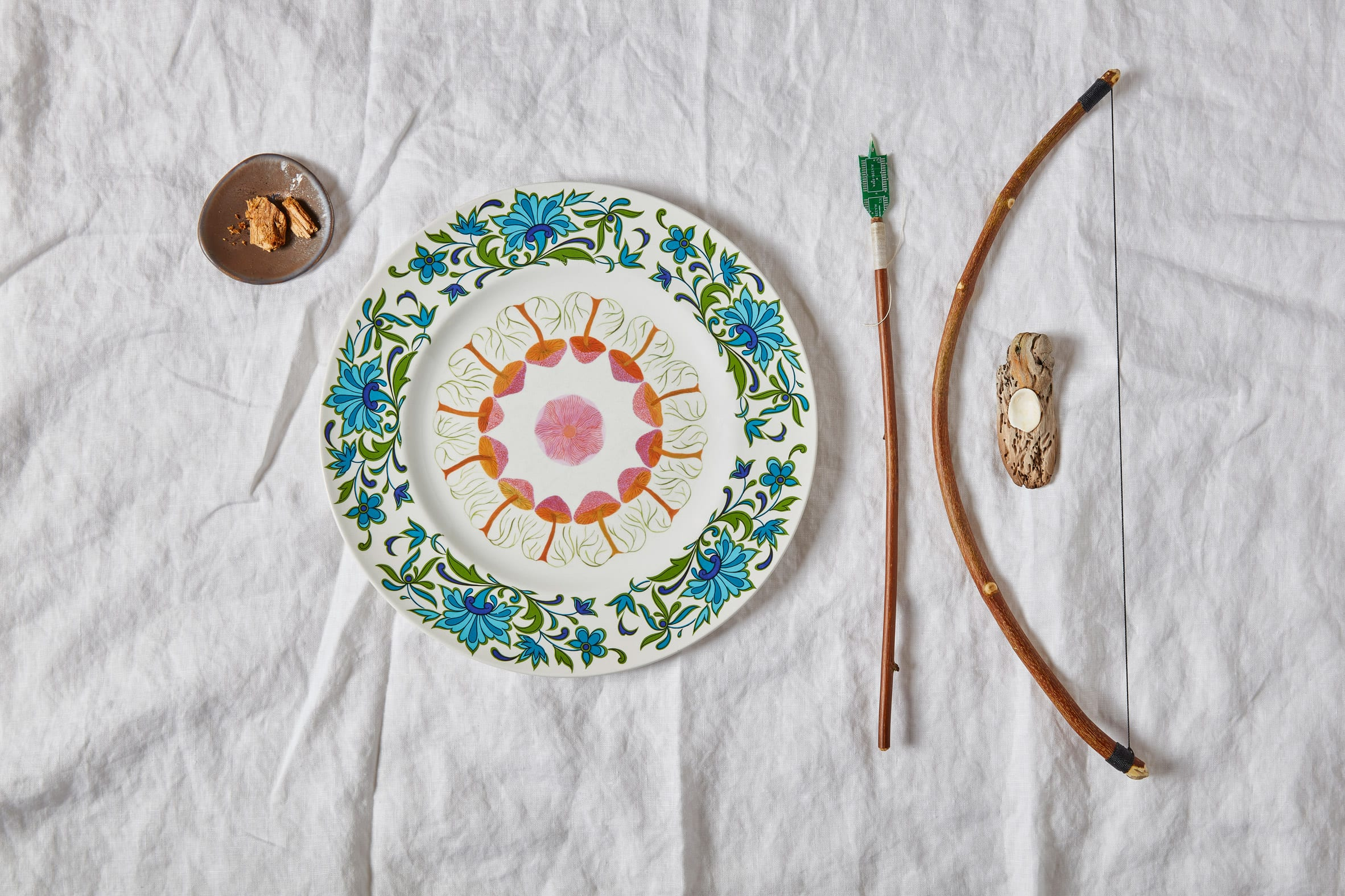 Close up of bespoke cutlery and colourful painted tableware from Refuge for Resurgence project