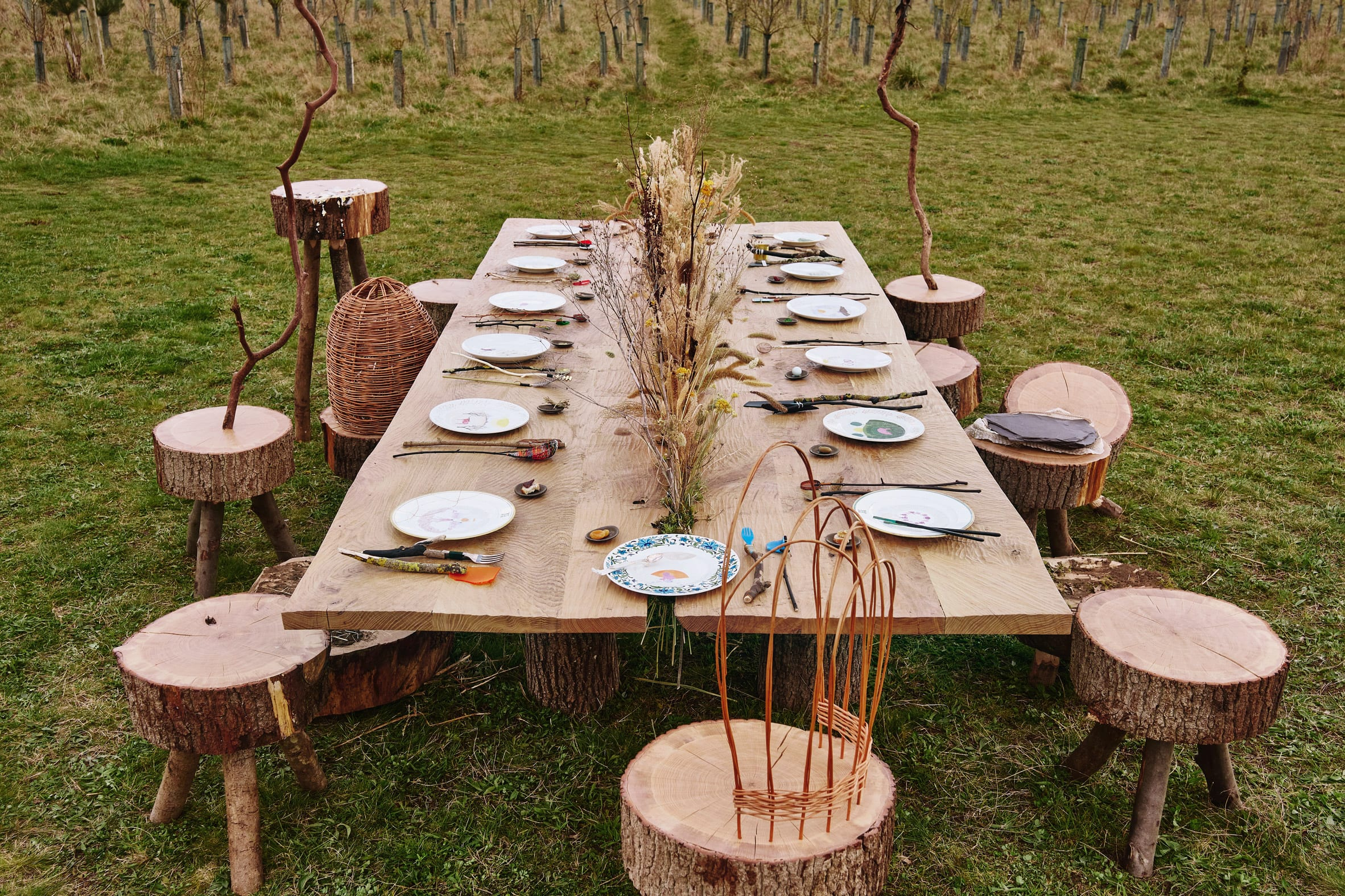 Wide view of stools gathered around wooden banquet table in Venice Architecture Biennale installation by Superflux