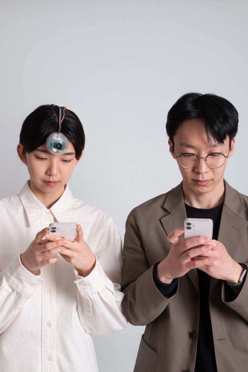 Woman wearing a robotic Third Eye looking at her phone next to man looking at his phone