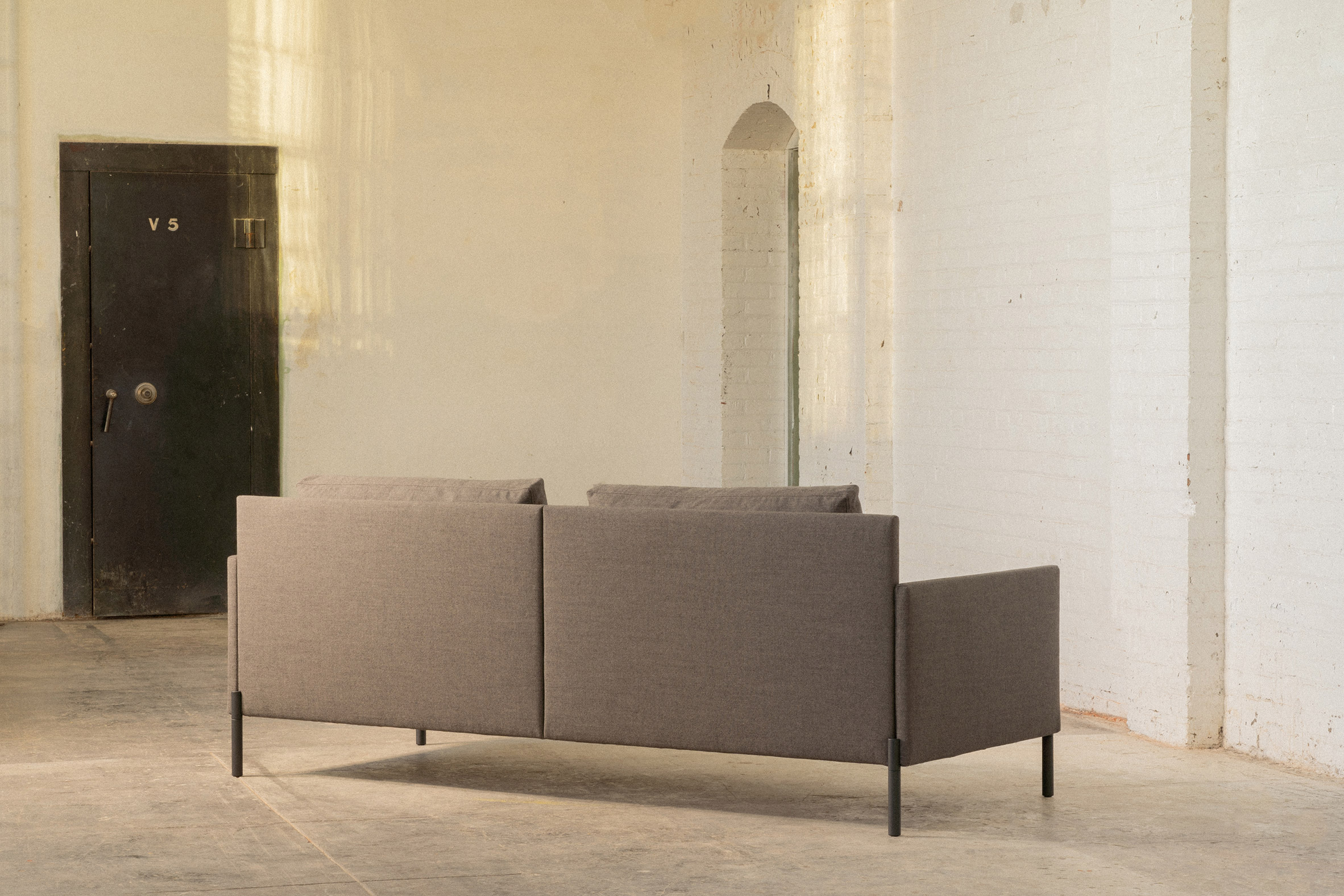 A straight back sofa with grey upholstery by Part & Whole