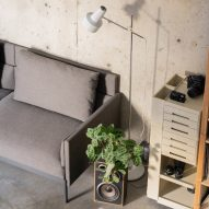 A concrete-walled room with a grey sofa