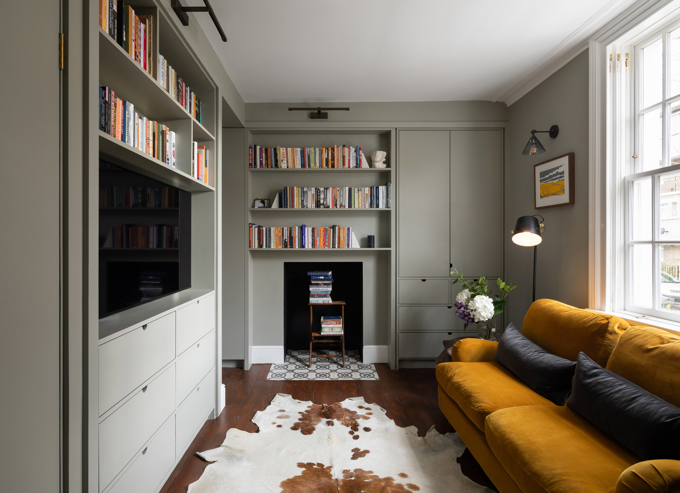 A living room with pale green cabinetry
