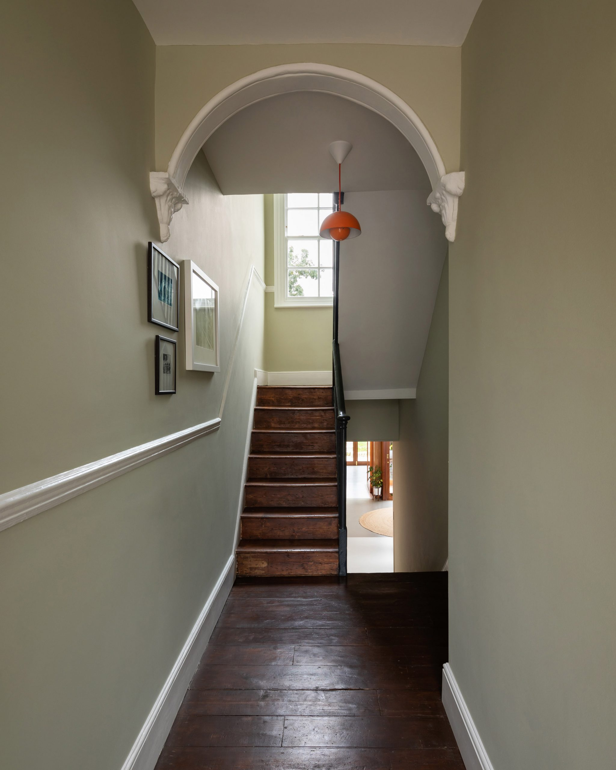 A hallway will pale green walls and hardwood floors