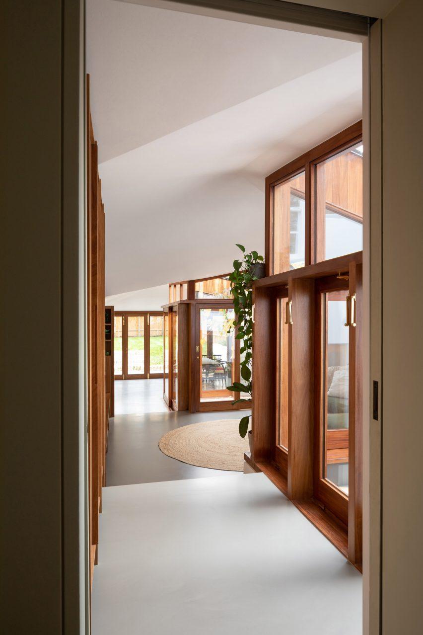 Lorong Rumah Tersembunyi dengan jendela dan pintu kayu gelap