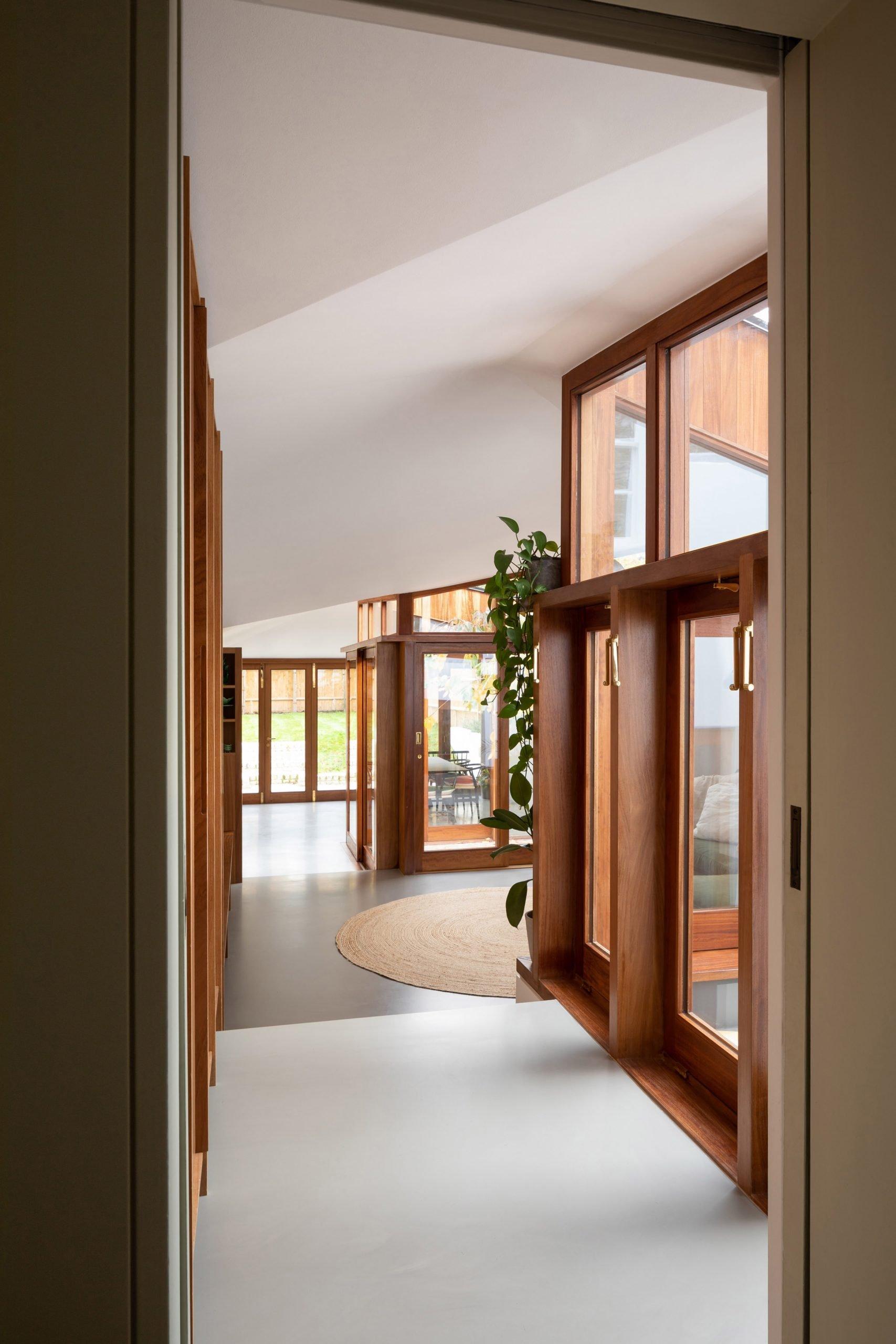 A Cloistered House's hallway with dark wood windows and doors