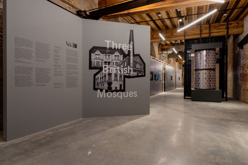 A grey wall contains an exhibition statement at the start of the pavilion