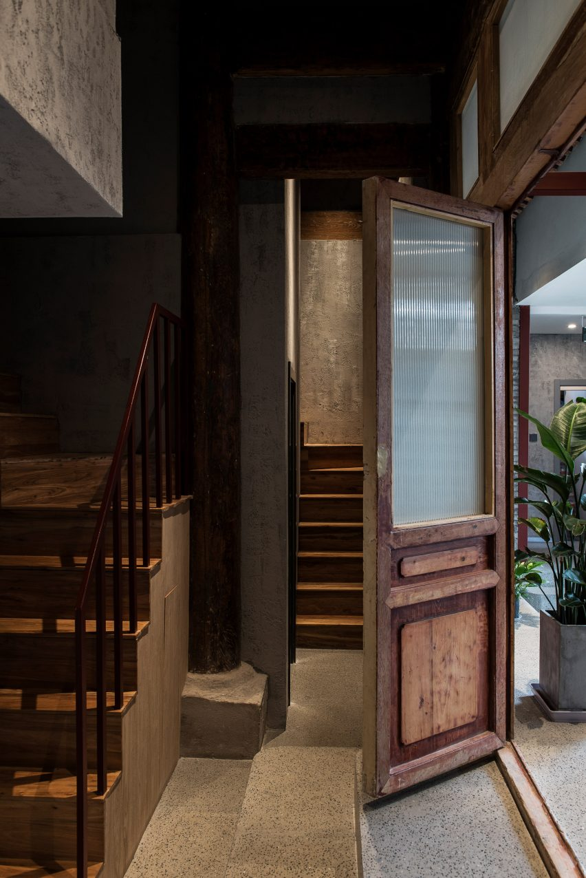 Entrance with wooden door and stairs to renovated hutong hotel by Fon Studio