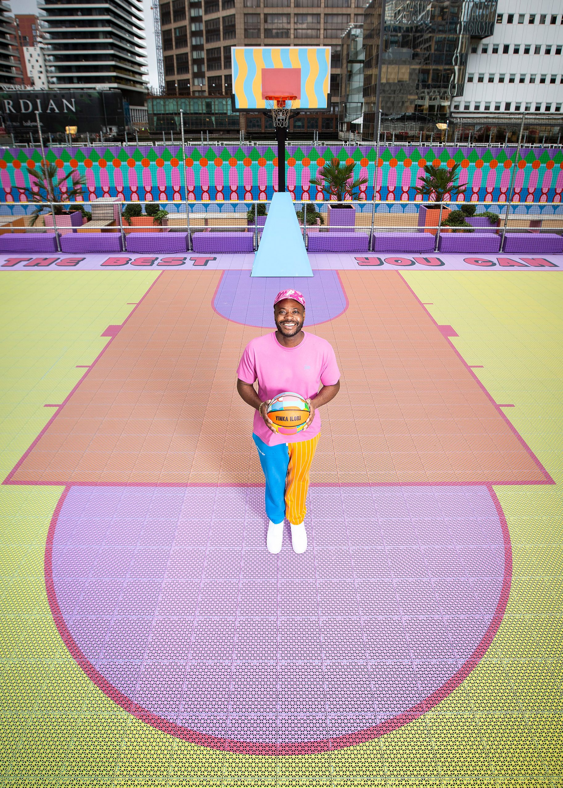 Aerial view of Yinka Ilori on colourful Canary Wharf basketball court