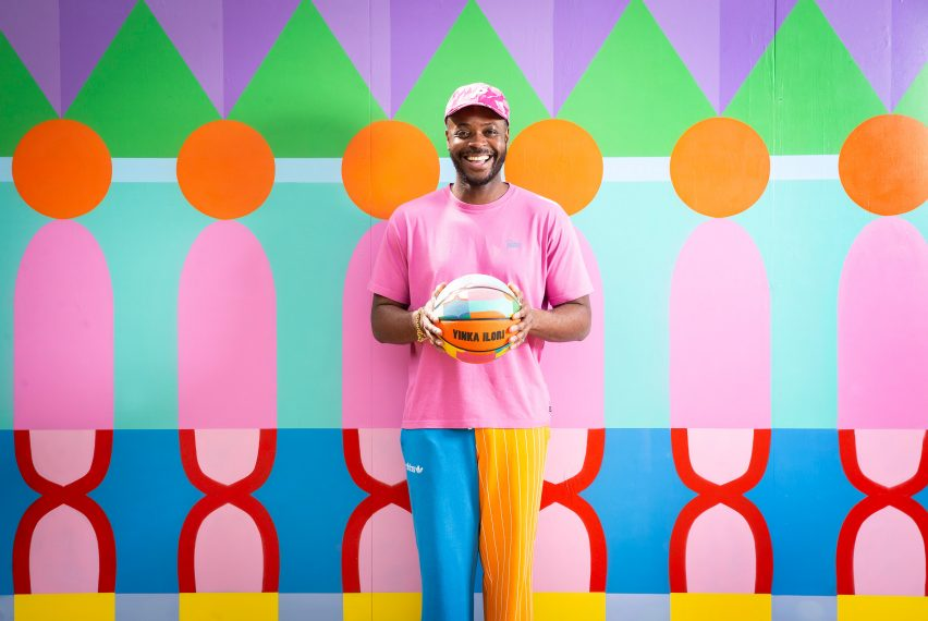 Yinka Ilori holding basketball in front of colourful printed hoarding