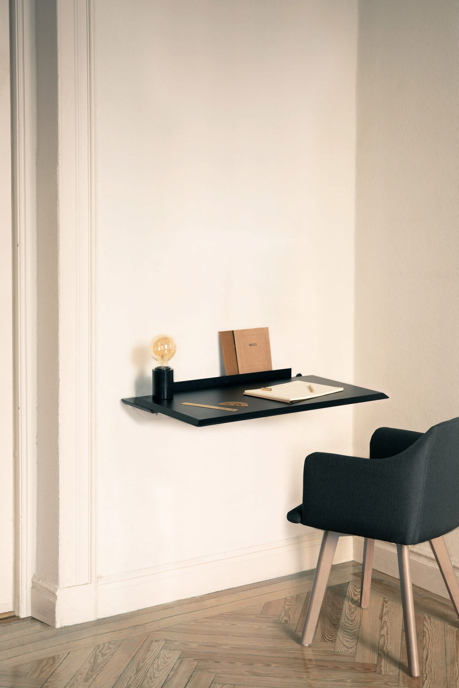Black version of the Alada desk folded out with stationary and lamp on top