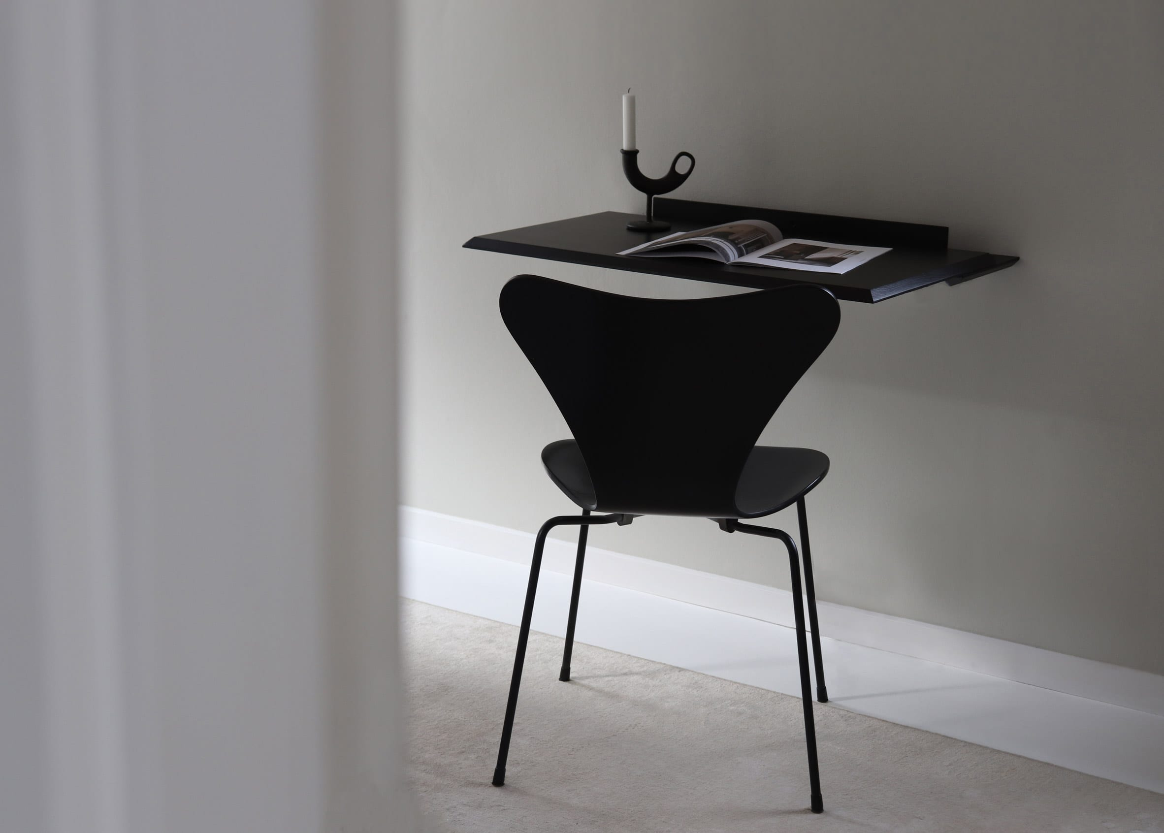 Black version of the Alada desk affixed to a wall with ornaments sat atop
