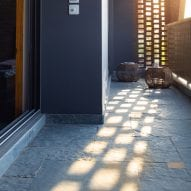 The brick screen allows light to dapple into the home