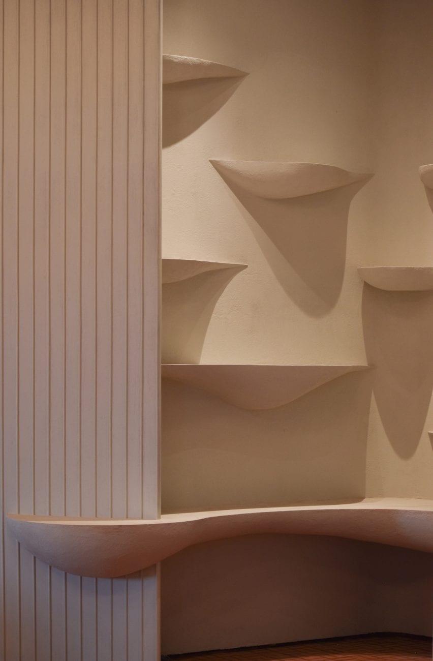 Integrated white shelves inside the restaurant by Ashiesh Shah