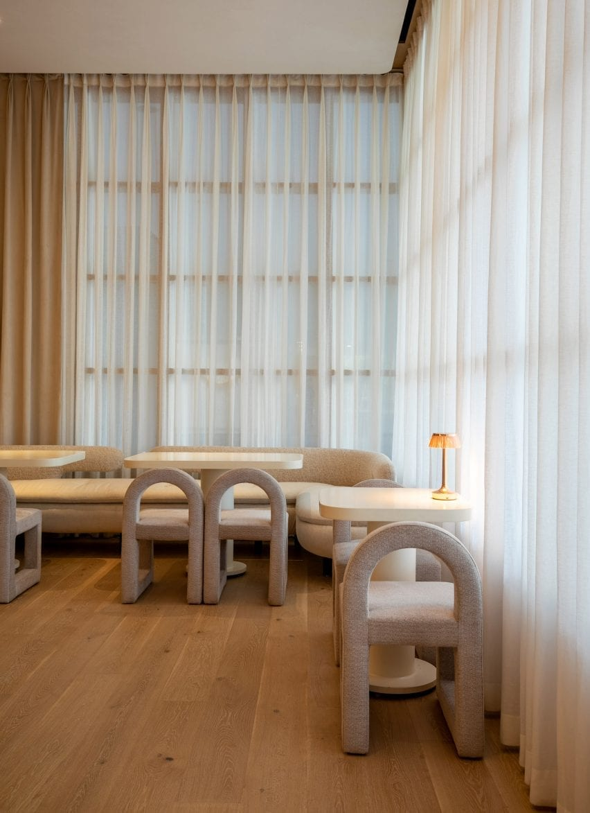 Seating area with sheer curtains and rounded seats in the restaurant by Ashiesh Shah