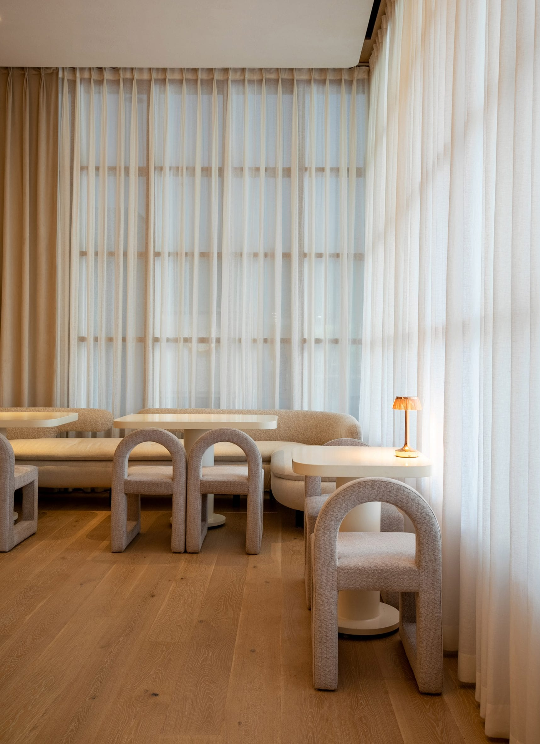 Seating area with sheer curtains and rounded seating in restaurant by Ashiesh Shah