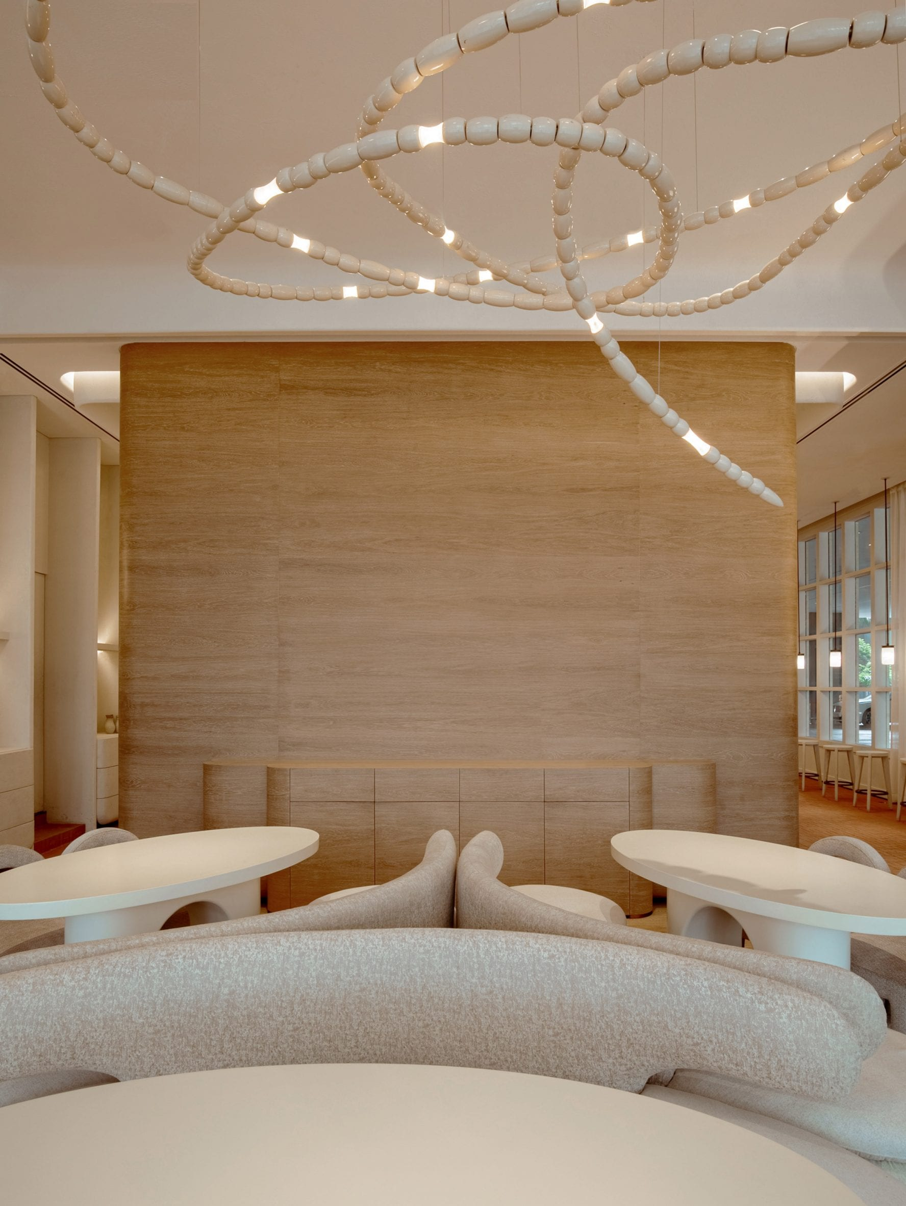 Seating area with oak veneer walls and sculptural chandelier made from wooden beads in restaurant interior by Ashiesh Shah