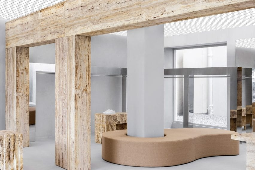 Travertine wall, mirrored clothes rail and upholstered bench in Axel Arigato Paris store